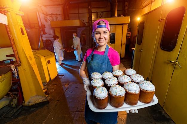 Поддоны с запеченной пасхой. промышленное производство куличей. пекарня.