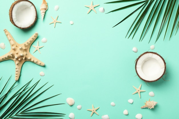 Palm branches, starfishes and coconut on green surface