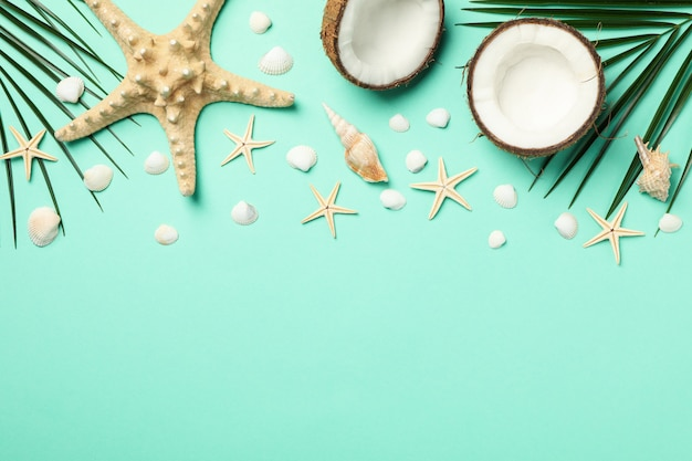 Palm branches, starfishes and coconut on mint, space for text