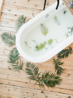 Palm branches with flowers top view in a bath tub and on wooden background