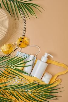 パーム、バケットサンハット、ストリングバッグに入ったspf日焼け止めクリーム、サングラス、ベージュの砂の表面にサージカルマスク