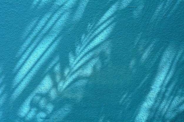 Palm coconut leaf shadow on blue cement wall