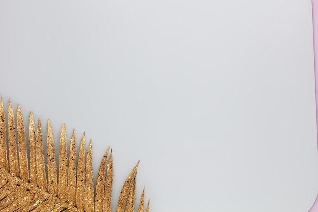 Сусальное золото пальмы на синем фоне. пальмовый лист, плоская планировка и вид сверху.
