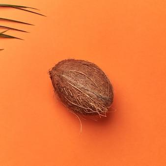 テキスト用のスペースがあるオレンジ色の背景にヤシの緑の葉と有機ココナッツ全体。フラットレイ