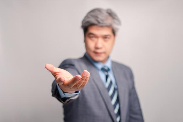 소송에서 아시아 수석 사업가의 손바닥 손. 연결, 기술 및 기업의 개념