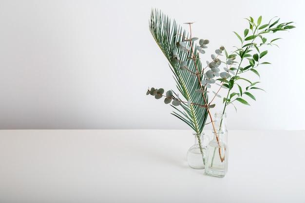 흰색 바탕에 유리 꽃병에 야자수 잎 유칼립투스와 녹지 꽃다발의 장식. 녹색 열대 식물 미니멀리즘. 복사 공간이 있는 흰색 테이블에 다양한 열대 잎과 식물을 놓습니다.