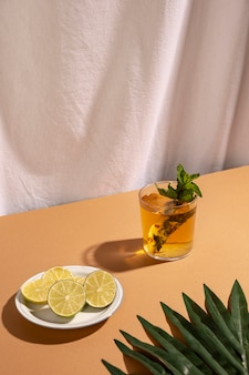 Palm leaf with lemon slices and cocktail drink over brown table