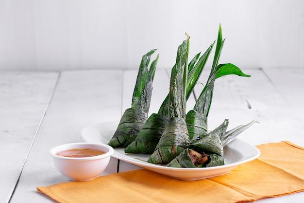 白いセラミックプレートに美しく配置されたヤシの葉で包まれた鶏肉
