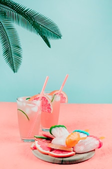 Palm leaves over the grapefruit cocktail glasses; popsicles on coral desk against teal background