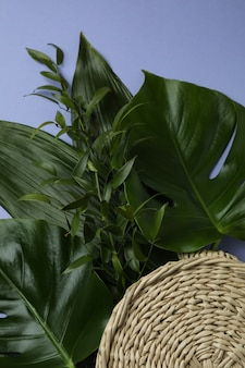 Palm leaves and straw bag on violet isolated background