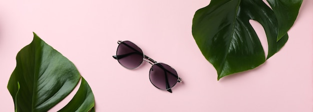 Palm leaves and sunglasses on pink isolated background
