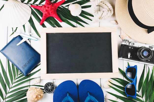 Palm leaves and travel supplies around blackboard