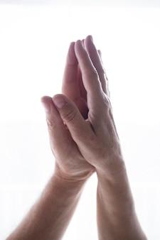 人間の手のひらは、白いコピースペースの背景の上にナマステの祈りの位置で一緒に結合しました。ウェルネスと健康的なライフスタイルの概念。祈りのポーズでヨガ瞑想をしている大人の手。