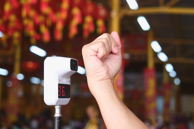Сканирование ладони на сканере термометра для проверки температуры тела с помощью инфракрасного цифрового термометра для скрининга лихорадки в общественном китайском храме во время эпидемии covid-19, мягкий и выборочный фокус