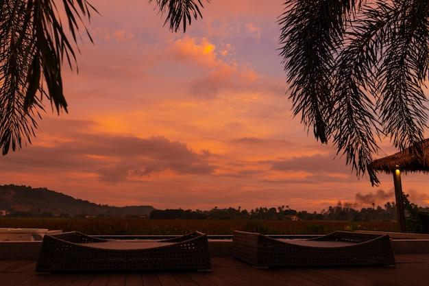 ヤシの木は、中庭のプールを見下ろす珍しい燃えるような赤い熱帯の夕日の背景にあります。