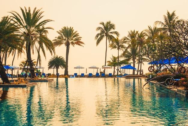 일출 시간에 고급 호텔 리조트에서 우산 의자 수영장이있는 야자수
