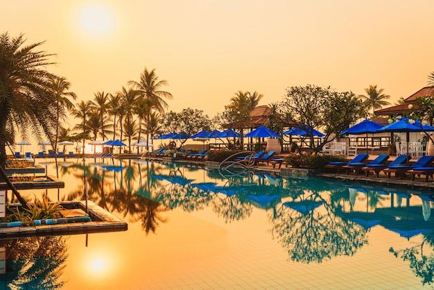 Пальма с зонтиком стул бассейн в роскошном отеле курорта во время восхода солнца
