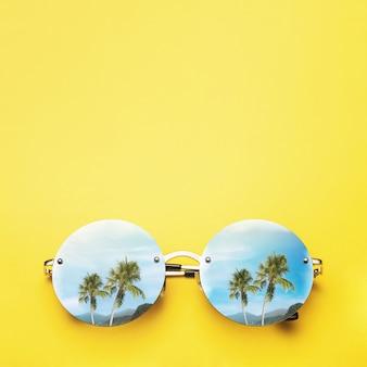 Пальмы и горы отражаются в солнцезащитных очках на желтом фоне, концепция отпуска и путешествий с копией пространства