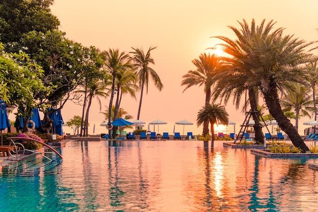 Пальмы с зонтиками и стульями у бассейна в роскошном курортном отеле на рассвете