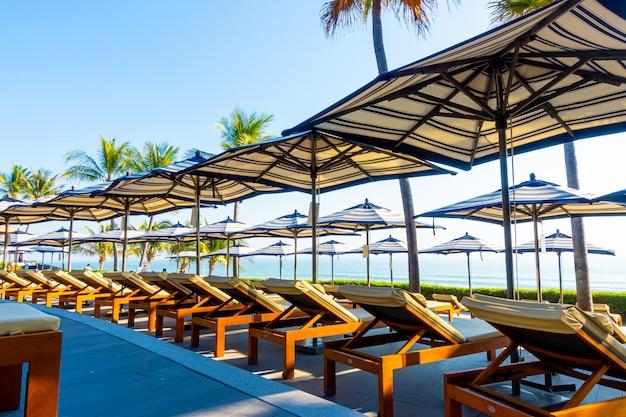 ココナッツpalm子の木とホテルとリゾートの屋外スイミングプールの周りの美しい豪華な傘と椅子