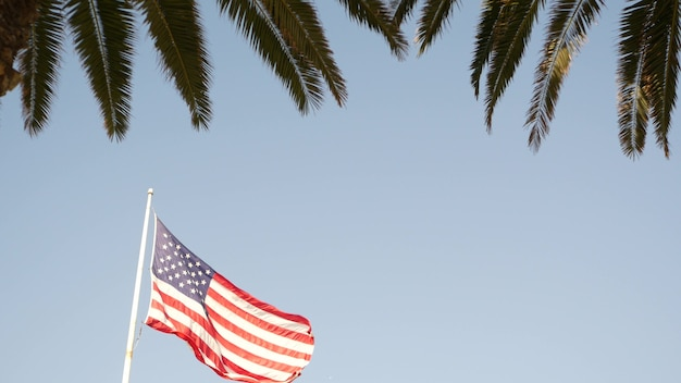 Palms and american flag, los angeles, california usa. summertime aesthetic of santa monica and venice beach. star-spangled banner, stars and stripes. atmosphere of patriotism in hollywood. old glory