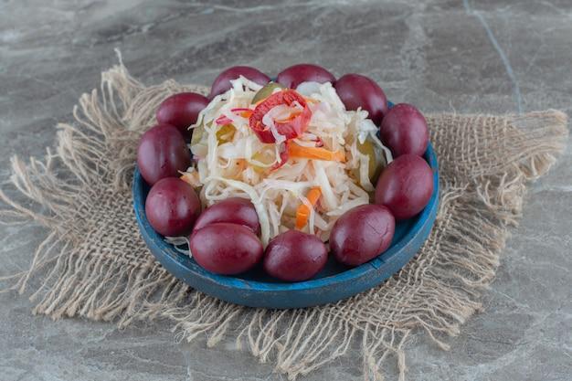 Пальмы вокруг квашеной капусты на деревянной тарелке.