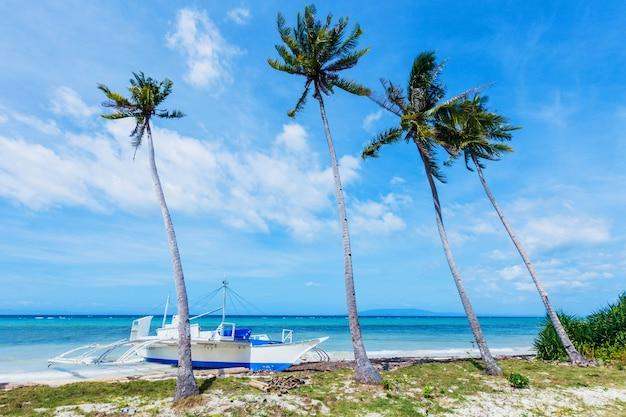 야자수, 아름다운 하얀 모래 해변, 보트가 있는 열대 바다