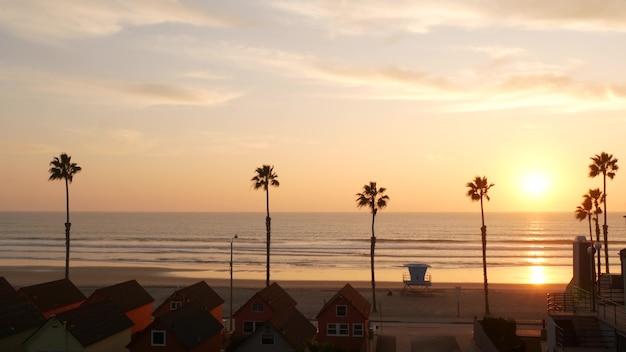 손바닥 실루엣 일몰 하늘, 캘리포니아 미학. 오션사이드 usa. 열대 태평양 해변 분위기. 로스앤젤레스 분위기. 인명 구조원 망루, 야자수 및 베이워치 타워 오두막. 해변가 코티지