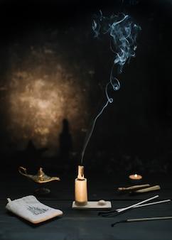 Палочка пало санто горит дымом в красивом подсвечнике