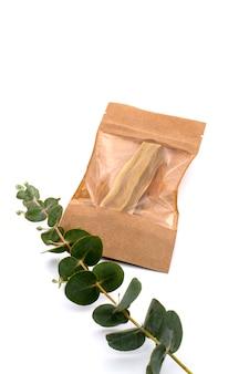 흰색 배경에 대해 공예 가방에 유칼립투스 나뭇가지가 있는 팔로 산토 나무 막대기
