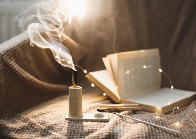 Деревянная палка пало санто горит дымом в красивом подсвечнике