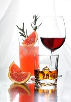 Коктейль палома в бокале коллинза виски в бокале с кубиками льда красное вино в бокале бордоской формы напитки