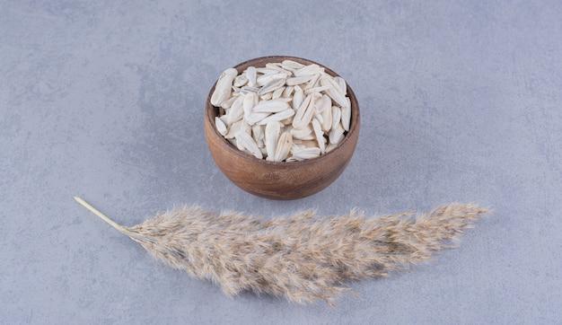 Erba della pampa e ciotola di semi di girasole sulla superficie del marmo