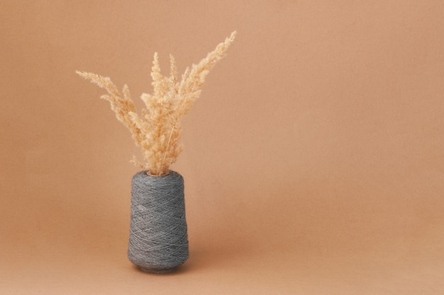 Pampas grass or dry reeds plums is made from a large spool of gray thick woolen thread or yarn on beige cardboard or paper