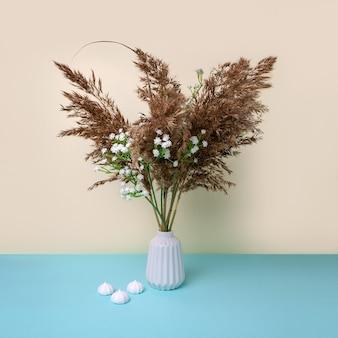 흰색 꽃과 머랭 미니멀리즘 꽃병에 팜파스 잔디.