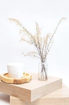 Трава пампасов в стеклянной вазе на деревянном столе у белой стены
