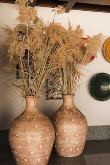 パンパスグラス、土鍋の葦植物。カラフルな装飾プレートを備えた伝統的なオリエンタルインテリアデザイン