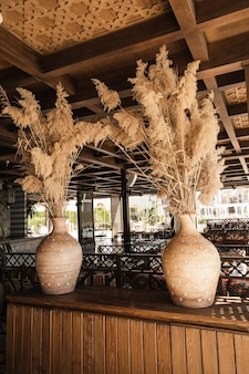 パンパスグラス、土鍋の葦植物。木製家具を備えた伝統的なオリエンタルインテリアデザイン