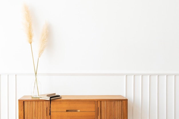 Pampas grass in a vase on a wooden sideboard table