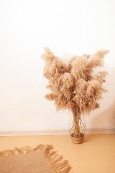 Камыши пампасов в стеклянной вазе. украшение сухой травой.