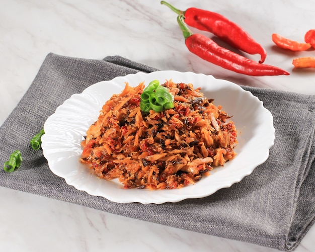 Pampis tongkol, manado's traditional seafood dish of spicy shredded fish, served on white ceramic plate. usually called tongkol suwir pedas