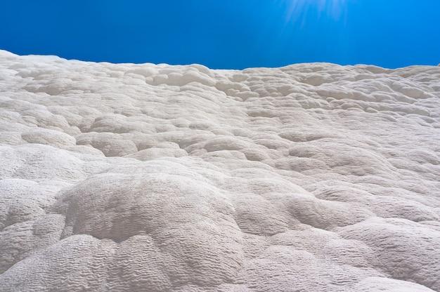 Памуккале, хлопковый замок, чудо природы создано слоями белого травертина, похожего на хлопок, турция. природная стена памуккале на фоне голубого неба