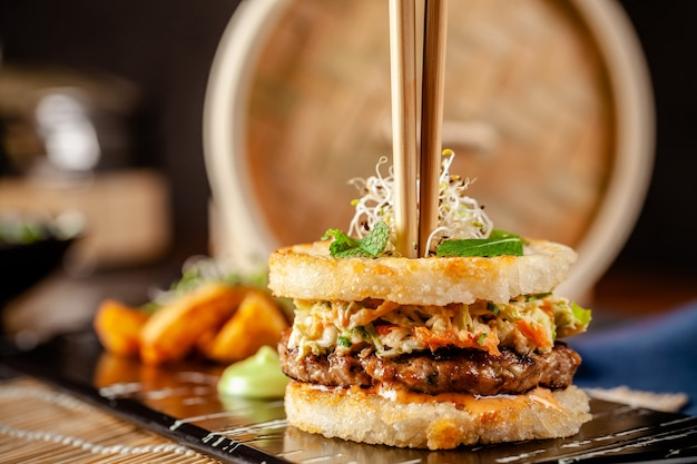 Pan-asian cuisine concept. japanese sushi burger made from rice bread, chicken and pork meat patties, lettuce and wasabi sauce. serving dishes with french fries. copy space