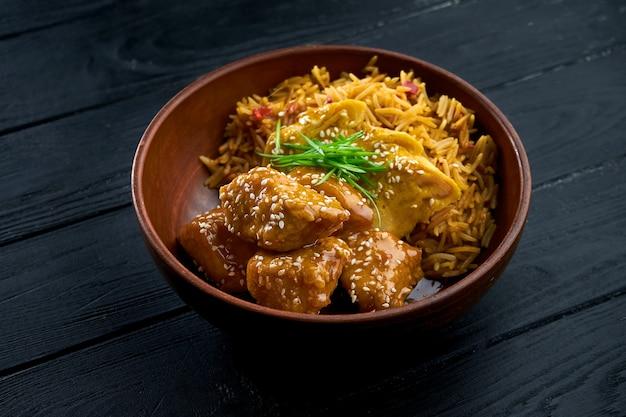 Паназиатская уличная еда - кисло-сладкая курица, украшенная рисом, подается в миске на деревянном фоне.