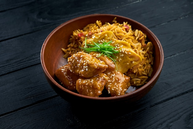 Pan-asian street food - sweet and sour chicken garnished with rice, served in a bowl on a wooden background.