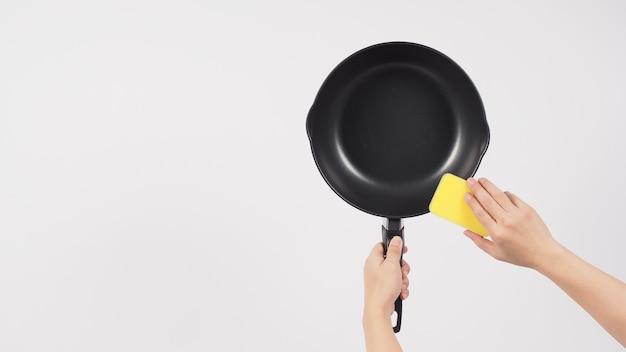 Рука человека для чистки сковороды на белом фоне, чистка сковороды с антипригарным покрытием губкой для мытья посуды