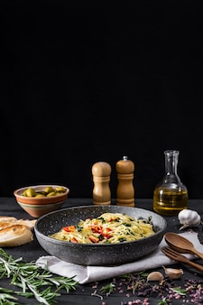 Pan of cooked italian pasta, copy space. traditional spaghetti meal with vegetables and olives on black rustic surface