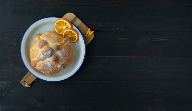 Pan de muerto on black background, typical mexican food. day of the dead celebration. copy space. top view.
