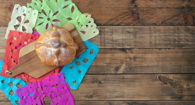 나무 배경에 있는 pan de muerto, 전형적인 멕시코 음식. 죽은 축하의 날. 공간을 복사합니다. 평면도.