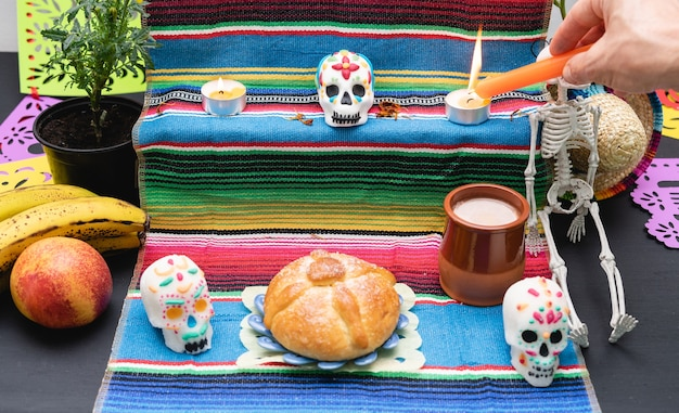 Pan de muerto, skulls and candles on a day of the dead altar. traditional mexican celebration.